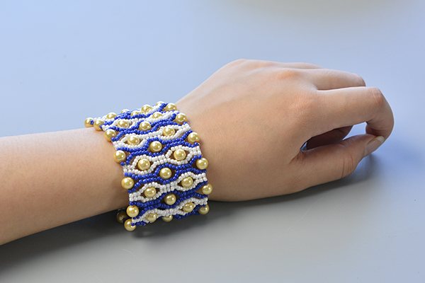 final look of the blue seed bead stitch wide bracelet with yellow pearl beads