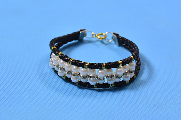 The final look of the black cord bracelet with pearls and rhinestones is displayed here. I guess you love it, right?