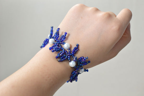 Now I'm showing you this purple seed bead tassel and white pearl bracelet on my wrist.