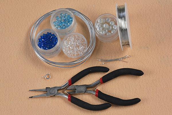 Supplies in making the wire wrap star bracelet with clear and blue glass beads decorated: