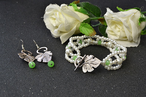 the white pearl bead bracelet and the leaf drop earrings