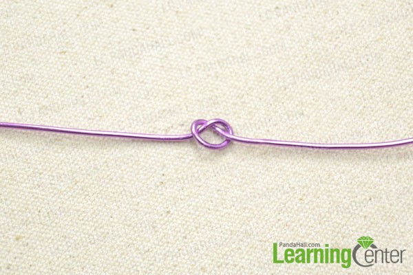 Cut a length of purple aluminum wire and tie an overhand knot