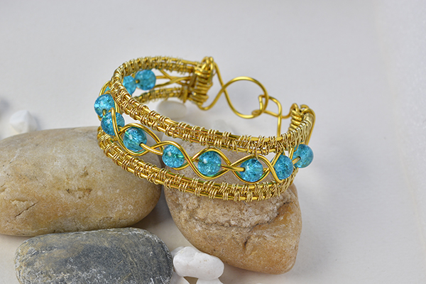 final look of the golden wire wrapped bracelet with blue crackle glass beads