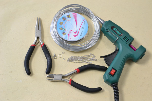 Supplies in making the creative wire wrapped heart pendent necklace with pink hot glue covered:
