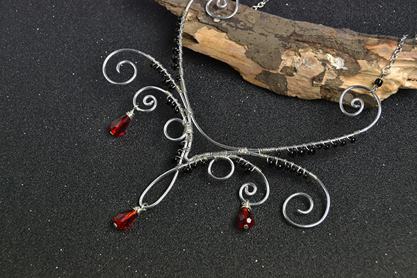 final look of the silver wire wrapped necklace with red drop glass beads